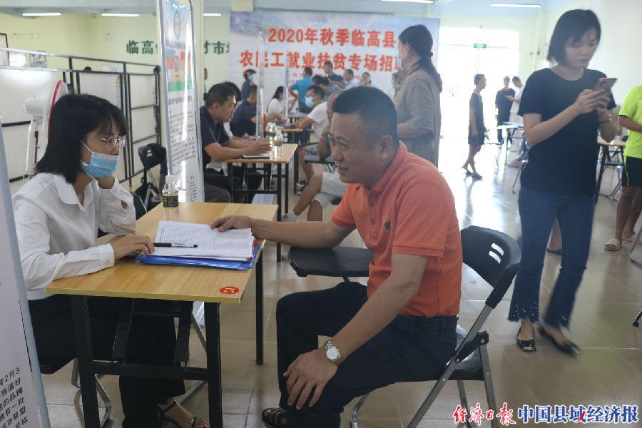 临高县人力资源服务中心主任林鸿刚向招聘工作人员了解企业用工需求(陈建峰 摄)