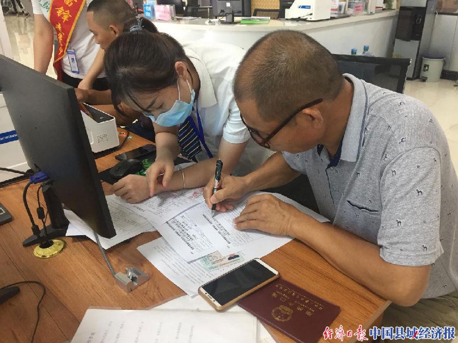 覃塘区政务服务导办人员协助群众填写办事表格